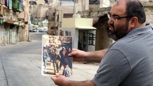 Yehuda Shaul visar en bild över hur livet var förut här på gatorna.