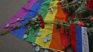 """En regnbågsflagga med blommor och ljus samt en rysk flagga med texten """"Ryssland är med USA"""" ligger på gatan utanför USA:s ambassad i Moskva, Ryssland."""