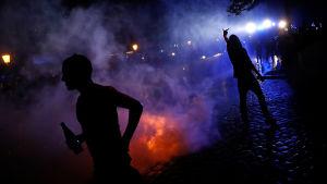 Demonstranter i motljus, en eld och vatten från vattenkanoner syns i omgivningen. En demonstrant visar tydligt mittfingret mot kameran.