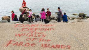 Turister vid Den lille havfrue som målats röd.