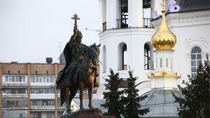 En staty som föreställer Ivan den förskräcklige i staden Oriel i Ryssland. I bakgrunden en kyrka med förgyllda kupoler