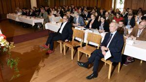 SDP:s Antti Rinne sitter på en stol och lyssnar med många andra människor.