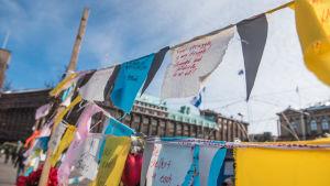 Tyglappar med text hänger på en byklina på Järnvägstorget i Helsingfors under demonstrationen mot avvisningen av flyktingar på Järnvägstorget i Helsingfors har pågått sedan februari.
