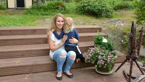 Kvinna med barn i famnen sitter på trappa utomhus