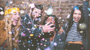 Neljä nuorta juhlatunnelmissa ja konfettia.