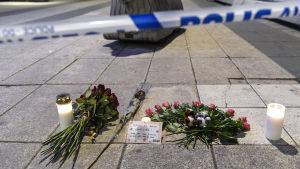 Ljus och blommor på nära Åhléns efter attacken i Stockholm den 7 april