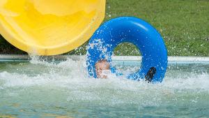 Barn simmar i vattnet med simring framför vattenrutschkana.