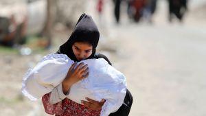 En ung irakisk flicka flyr sitt hem i västra Mosul med en baby i famnen 1.6.2017.