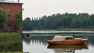 Gammal träbåt förtöjd i vindstilla havsvik intill rödtegelbyggnad.