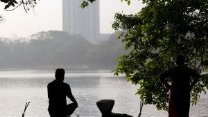Man idkar yoga i vid en sjö i Calcutta