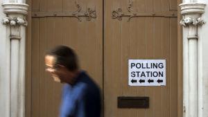 En man går förbi en skylt som pekar mot en val vallokal.