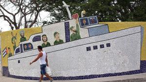 En man passerar ett mosaikarbete i Havanna som visar Che Guevara, Raúl och Fidel Castro. Lördagen 16.4.2016
