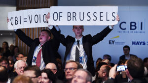"""Häcklare lyfter upp en banderoll med texten """"CBI = Bryssels röst"""" under premiärminister David Camerons tal på en CBI-konferens i november 2015"""