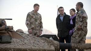 Kronprinsessan Victoria och prins Daniel står tillsammans med två svenska soldater vid en pansarvagn under ett besök i Afghanistan.