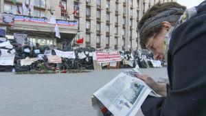 Kvinna läser en tidning utanför en myndighetsbyggnad i Donetsk i Ukraina.