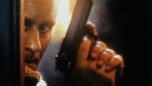 Stellan Skarsgård poserar med pistolen i högsta hugg.