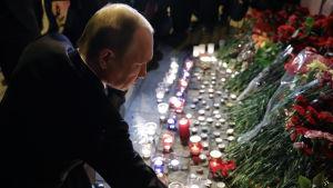 Putin lägger ner blommor utanför metrostation efter attacken i S:t Petersburg.