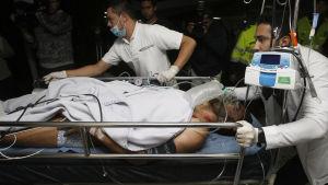 Alan Ruschel, en av de överlevande efter flygplanskraschen i Colombia, transporteras på bår.