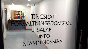 Dörren in till Ålands tingsrätt. På glasdörren står med stora svarta bokstäver tryckt: Tingsrätt, förvaltningsdomstol, salar, info, stämningsman.