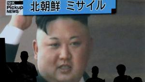 Fotgängare i Tokyo passerar en TV-skärm som visar Kim Jong-un 4.7.2017