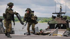 Två finska soldater kliver av en stridsbåt under en krigsövning. En chef övervakar övningen.