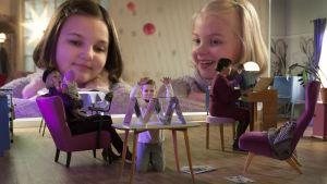 Onneli och Anneli kikar in i dockskåpet där en pysslingfamilj huserar