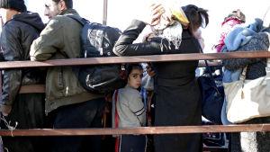 Flyktingar väntar vid gränsen mellan Syrien och Turkiet.