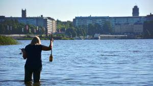 Ulla Udd, miljöingenjör för Vasa stad, tar algprover vid paradisön i Vasa.