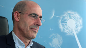 Mehmet Tanriverdi i profil mot en blå bakgrund. Han är vice ordförande för det kurdiska samfundet i Tyskland.