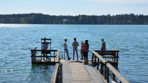 Några personer står ute på en lång brygga och samtalar och tittar ut mot vattnet.