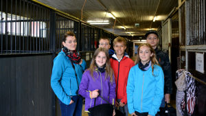 En grupp med människor i färggranna kläder inne i ett stall