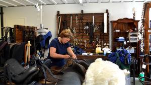 Kvinna i mitten av sadelmakeri reparerar sadel