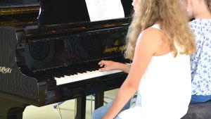 Två flickor sitter vid ett piano