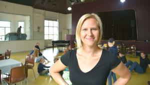 Sandra långbacka i förgrunden, i bakgrunden suddigt en stor sal med barn sittandes på golvet