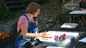 Flicka sitter vid träbord och ritar