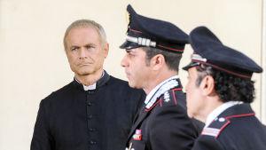 Isä Matteo (Terence Hill), kapteeni Tommasi (Simone Montedoro) ja ylivääpeli Cecchini (Nino Frassica) sarjassa Isä Matteon tutkimuksia