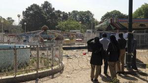 Människor tittar ut över den avspärrade nöjesparken i Lahore där självmordsattentatet inträffade på söndagen (bild 28.3.2016)