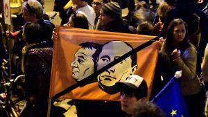 Demonstranter bär på en flagga med en bild på premiärminister Viktor Orbán och Rysslands president Vladimir Putin.