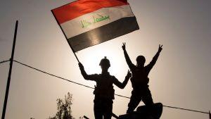 Irakiska regeringsstyrkor viftar med nationsflaggan i Mosul.