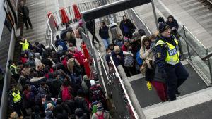 Polisen leder flyktingar ut från ett tåg som kommit från Danmark till Hyllie i Malmö. November 2015