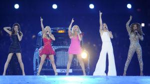 De fem damerna i gruppen sjunger på scenen vid avslutningskonserten av olympiska spelen i London år 2012, i bakgrunden en engelsk taxibil med registernumret SPICE