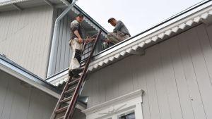 Män målar hus