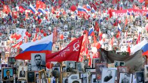 Deltagare i minnesmarschen på Röda torget i Moskva under Segerdagen bär på fotografier av anhöriga som deltog i andra världskriget.