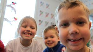 Esikoululaiset hymyilevät.