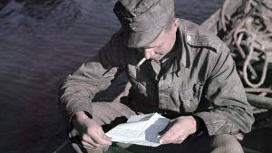 En soldat läser ett brev sittande i en båt.