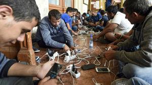 Flyktingar får ladda sina telefoner på järnvägsstationen i Budapest.