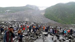 Räddningsarbetare och lokala invånare letar efter överlevande efter jordsredet i byn Xinmo i Maoxian i sydvästra Kina.