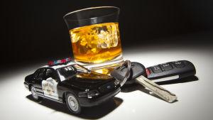 Ett glas whisky, ett par bilnycklar och en leksakspolisbil.