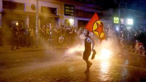 En demonstrant viftar med en rödgul flagga, framför en eld som demonstranterna startat på gatan i Hamburg.