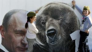 Barn i Moskva leker vid en plach föreställande president Putin och en björn.